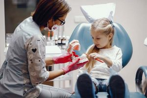 The little girl tries to follow the instruction given by the dentist.